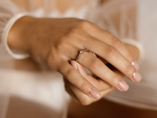 Tender girl's hands with engagement ring with diamond and beautiful manicure