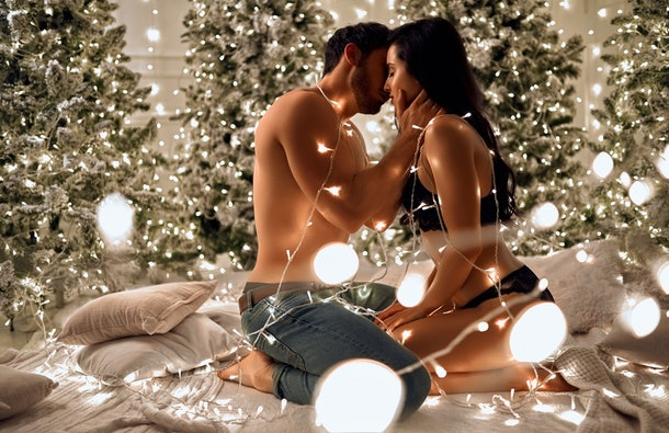Merry Christmas and Happy New Year! Sexy passionate couple celebrating Christmas together. Attractive woman in lingerie and handsome bearded man having sex on background of decorated New Year trees.