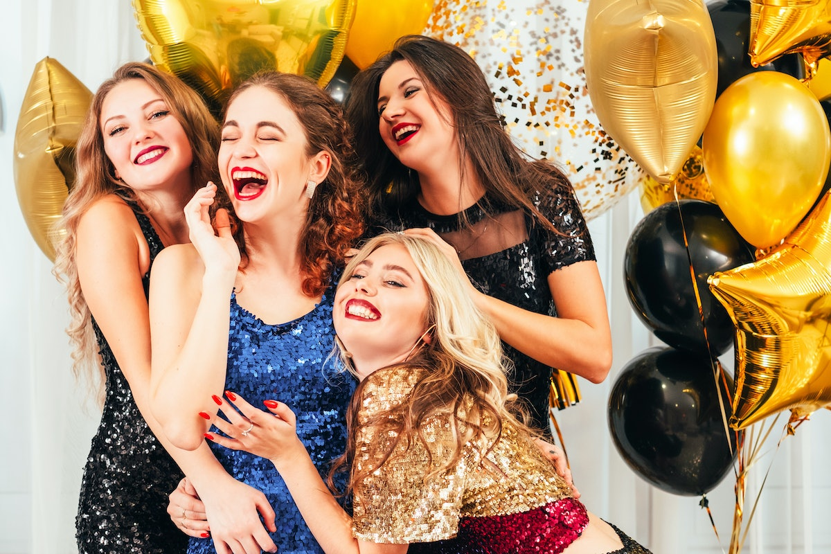 Friends wearing sparkly dresses pose with balloons at a birthday party.
