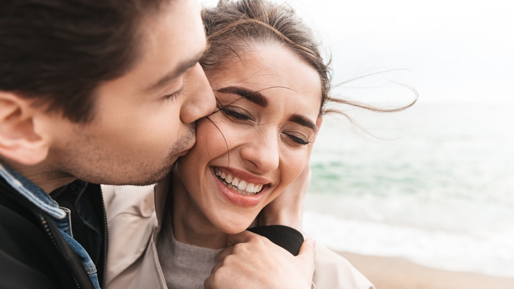Happy lovely young couple wearing coats walking at the beach, holding hands, embracing, kissing