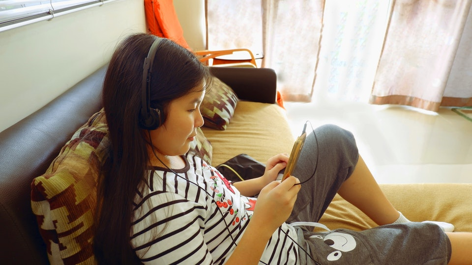 Young teen girl listening to audiobook on headphones