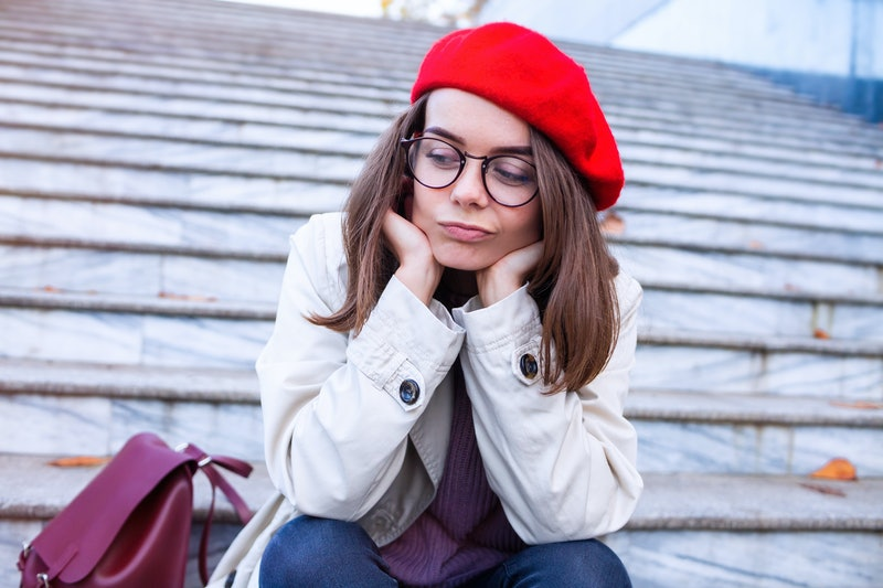 sad woman in glasses sitting on the stairs