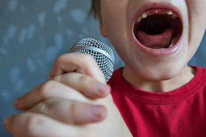charming kid sings into microphone and opens her mouth wide with milk teeth dropped out.