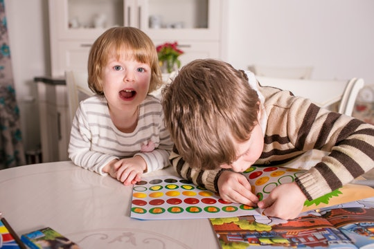 two kids playing with sticker books
