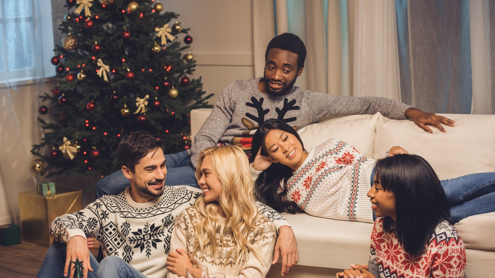 A group of friends in ugly Christmas sweaters relax in the living room next to a Christmas tree.