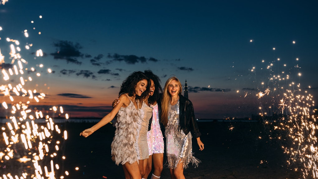 Three friends in sparkly dresses dance on the beach on New Year's Eve around sparklers and fireworks.