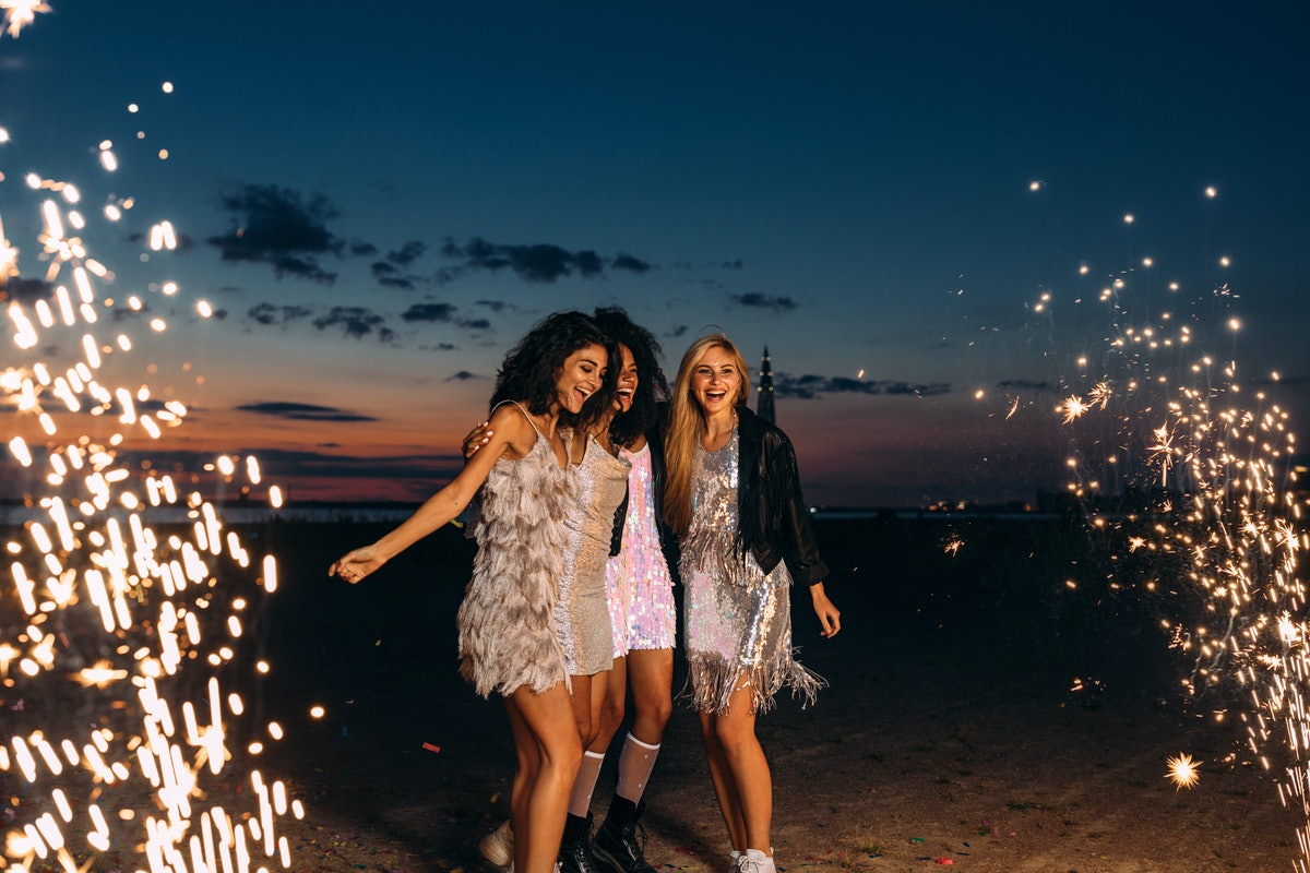Three friends in sparkly dresses dance on the beach on New Year's Eve around sparklers and fireworks...