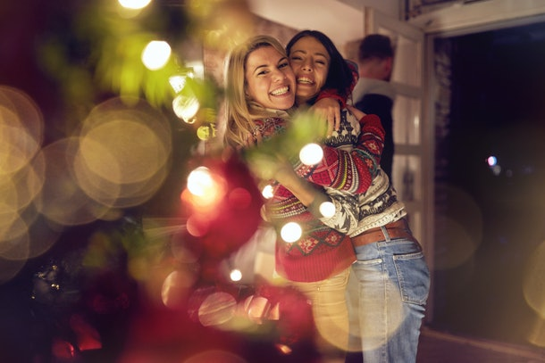 Two girls wearing ugly Christmas sweaters smile and hug next to a Christmas tree.