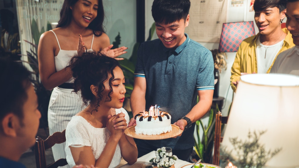 Friends celebrate a birthday at a dinner table while the birthday girl blows out the candles.