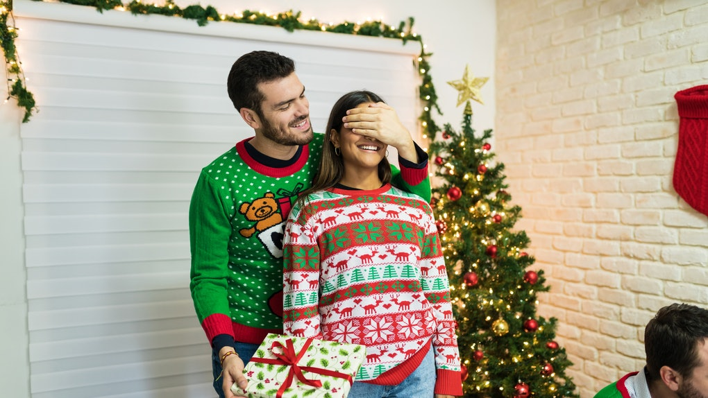 A guy surprises his girlfriend with a present while they're both dressed in ugly Christmas sweaters.