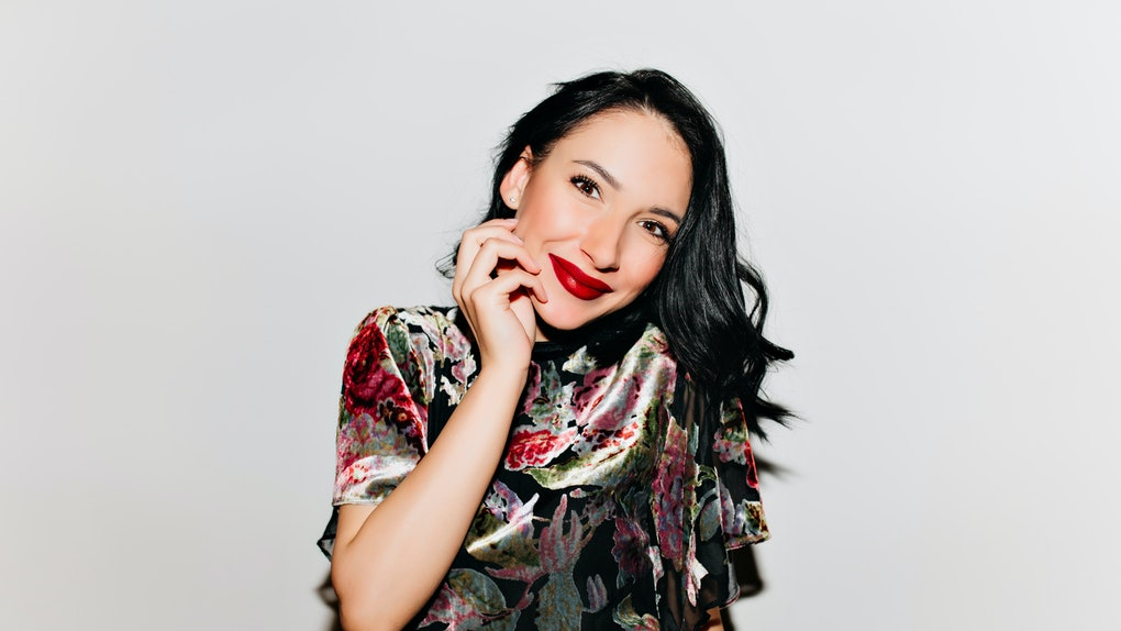 Glamorous black-haired woman with bright makeup posing with surprised smile. Glad female model with dark hair touching her face and laughing on white background.