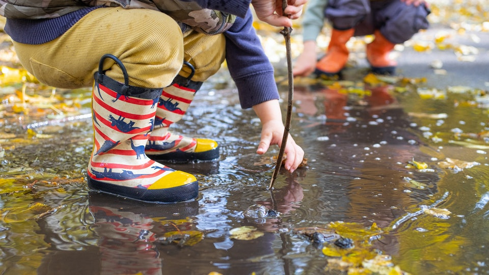 kids legs in rubber rain boots in puddle in autumn