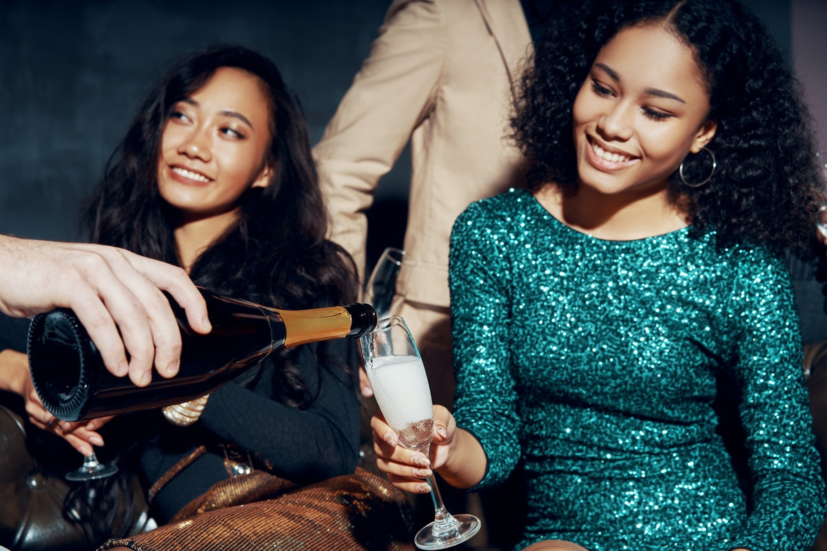 Two girls sit on a couch on New Year's Eve holding their champagne glasses.