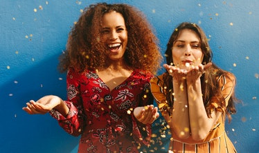 Two girls laugh and blow glitter and confetti into the air.
