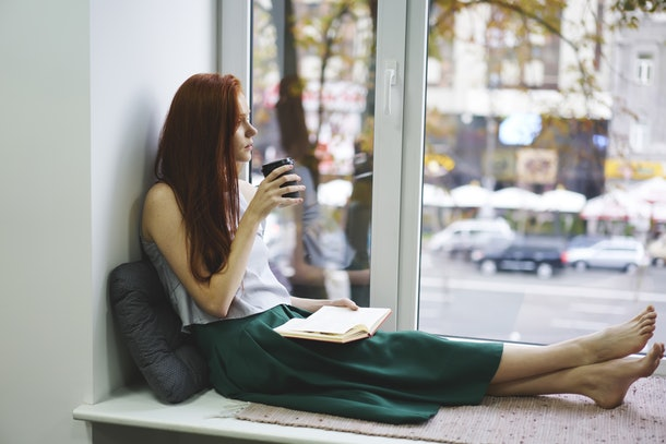 Thoughtful female foxy author looking out of window while drinking tasty aroma coffee and thinking about plot of book,pensive student dreaming and enjoying autumn weather sitting on windowsill
