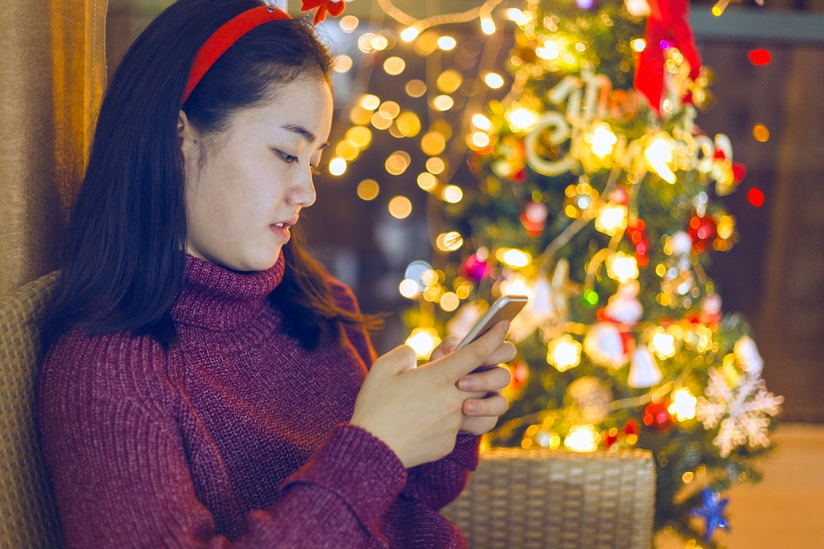An Asian woman operates mobile devices on Christmas Eve.