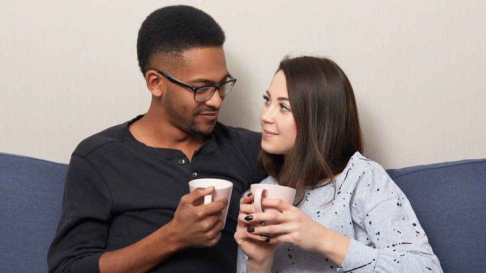 Horizontal shot of lovely multiethnic girlfriend and boyfriend drink coffee or tea together, pose at comfortable couch, look at each other with love, enjoy comfort, togetherness. Interracial relations