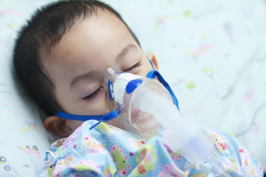 A sleeping baby receiving a breathing treatment