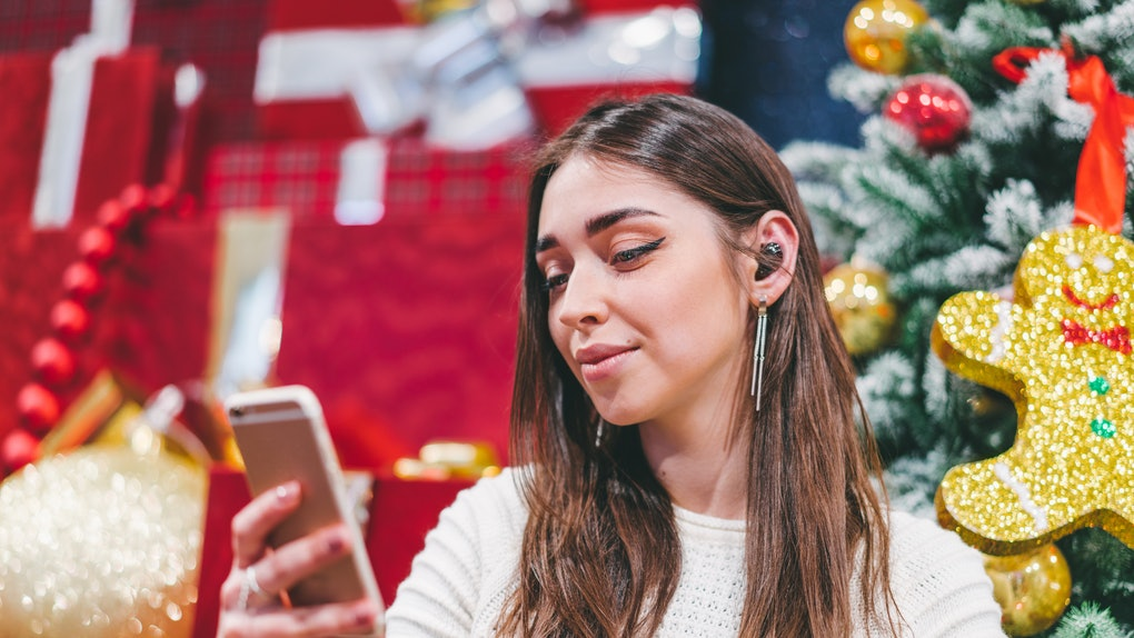 Young smiling attractive girl sitting near christmas background, having video conference with her friends to congratulate them, using mobile phone and wireless headset.