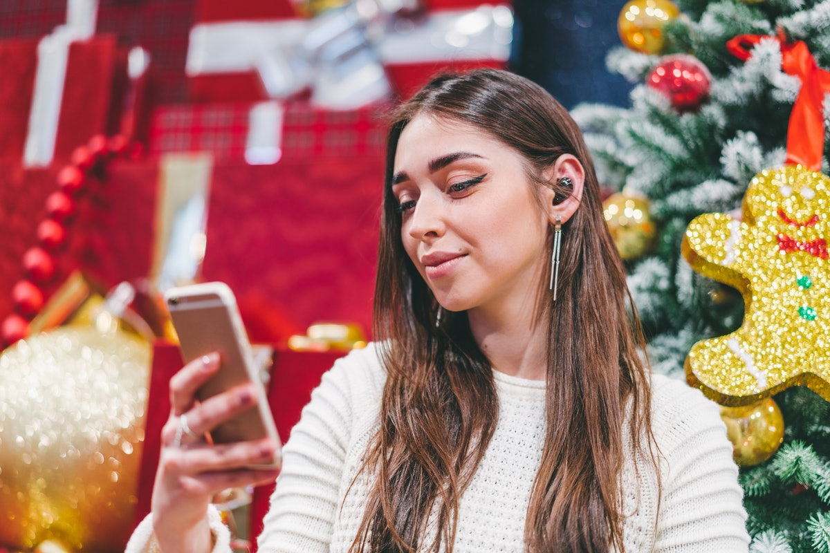 Young smiling attractive girl sitting near christmas background, having video conference with her fr...