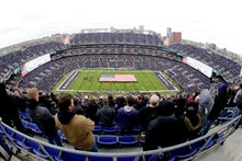 U.S. service members hold a large flag on the field at M&T Bank Stadium as part of the Baltimore Rav...