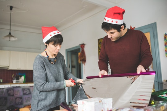 a couple wearing santa hats, wrapping presents