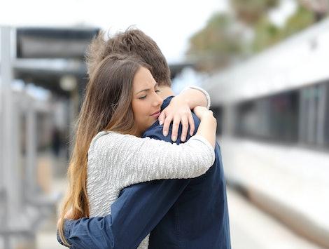 Sad couple hugging saying goodbye before train travel