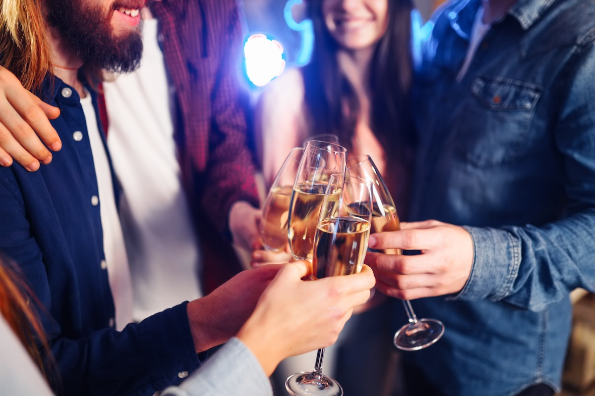 New year glasses for champagne in the hands of friends. Christmas New Year's toast. Friends With Dri...