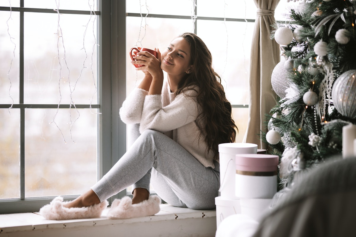 A woman dressed in comfy clothes and fuzzy slippers sits on a windowsill and holds a red mug at a be...