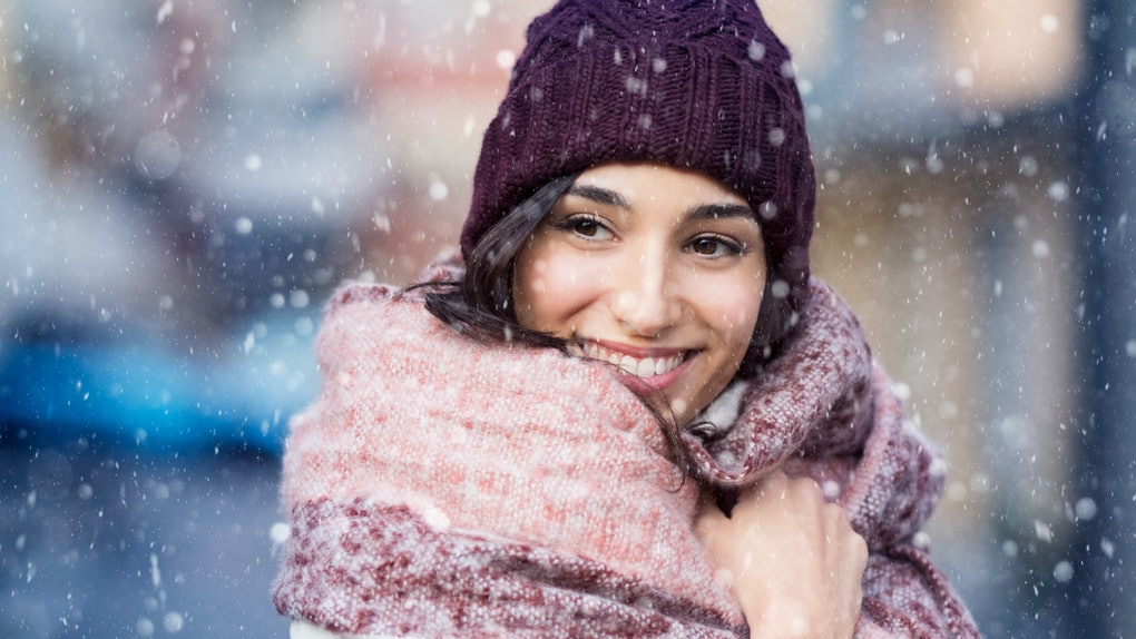 Smiling woman wearing wool bonnet and scarf in a winter cold day. Happy girl in a sweater outdoor in snow. Beautiful smiling woman with hat and scarf outdoor looking away.