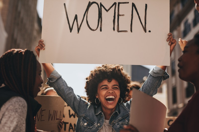 Laughing young woman holding a banner during a protest. Group of females activist protesting on road...