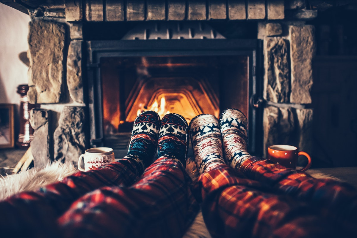 Two people wearing flannel PJs and cozy socks sit next to the fireplace in a bed and breakfast over ...