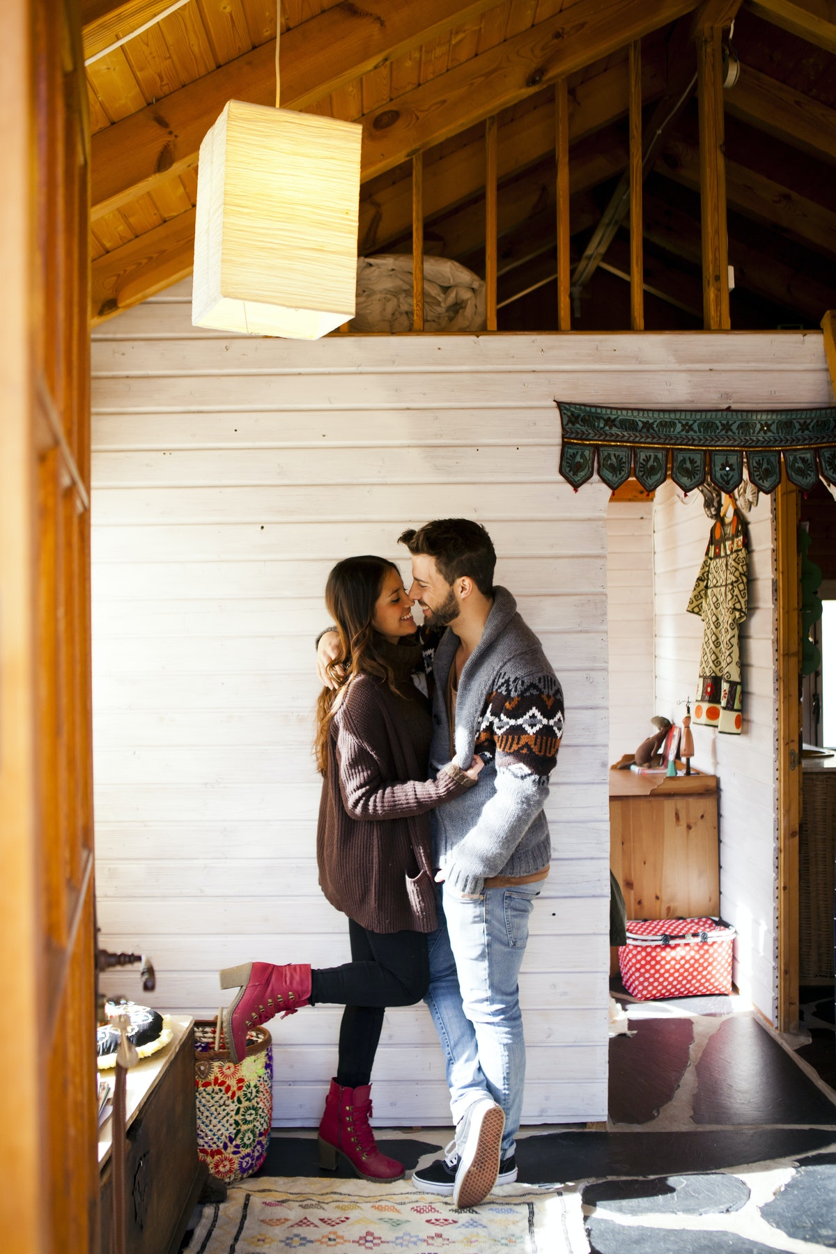 A couple shares a romantic moment while hanging out in a cabin during a winter getaway.