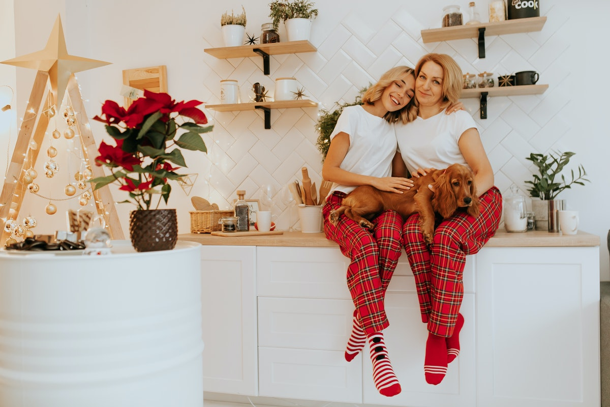 A mother and daughter sit in holiday pajamas with their dog on their kitchen counter.