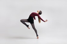 young beautiful woman dancer with long brown hair wearing maroon swimsuit posing on a light grey stu...