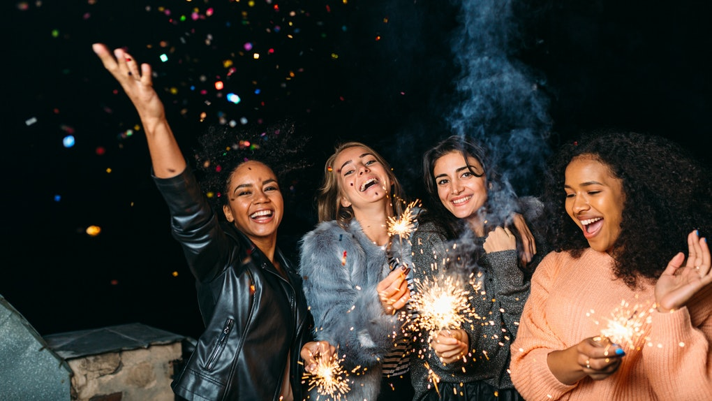 A group of friends celebrate New Year's Eve outside with sparklers and confetti.