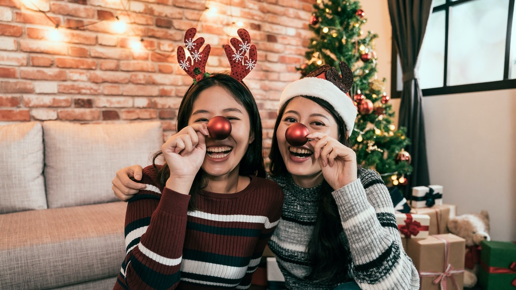 Content young asian women embracing while sitting on floor and making noses with red tree baubles. happy xmas girls in santa reindeer hats laughing having fun face camera. merry christmas new year