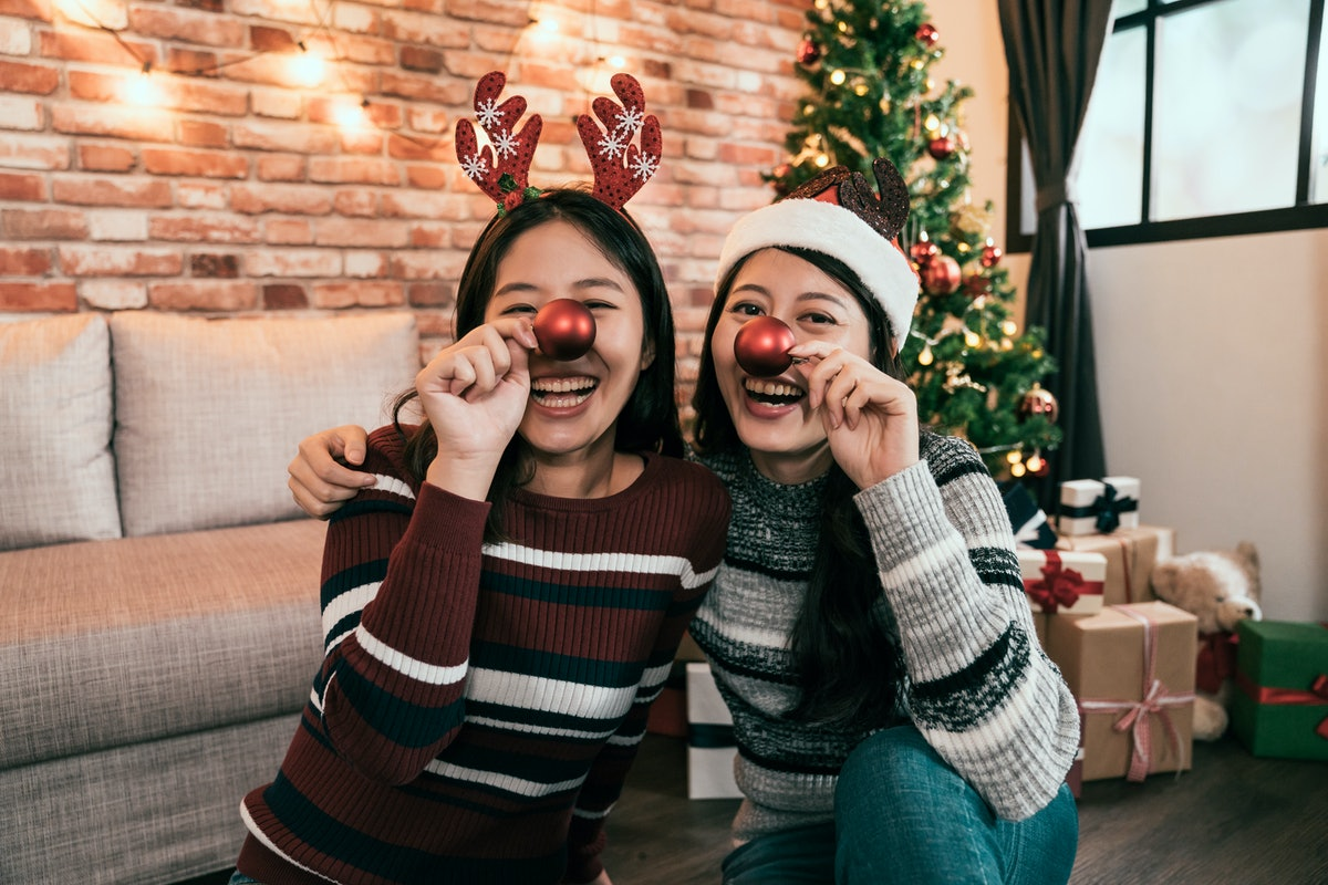 Sisters wearing red noses at Christmas to post on Instagram with reindeer puns and reindeer quotes.