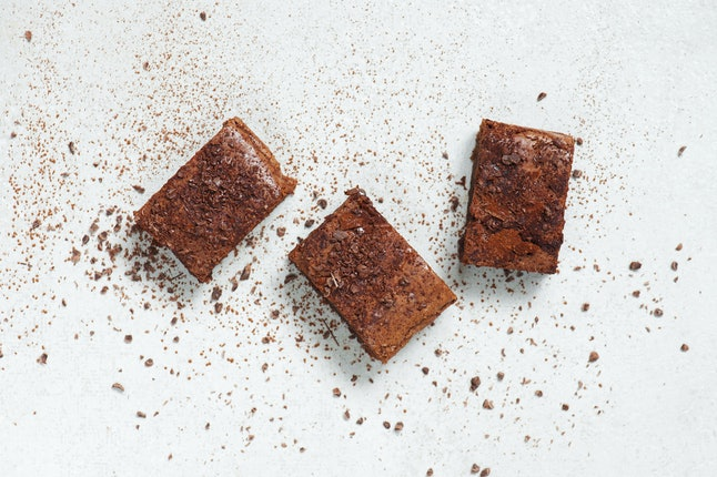 Three pieces of brownie topped with chocolate chips and cocoa on the light table