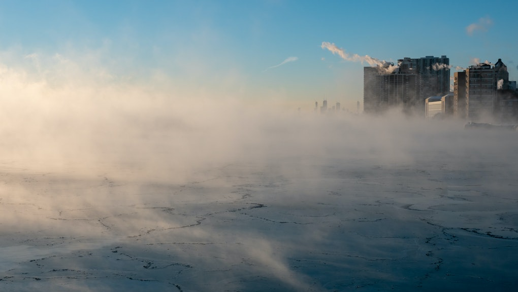 Chicago skyline in the distance from the far north lakefront on a frigid morning over a steaming lake