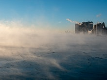 Chicago skyline in the distance from the far north lakefront on a frigid morning over a steaming lak...
