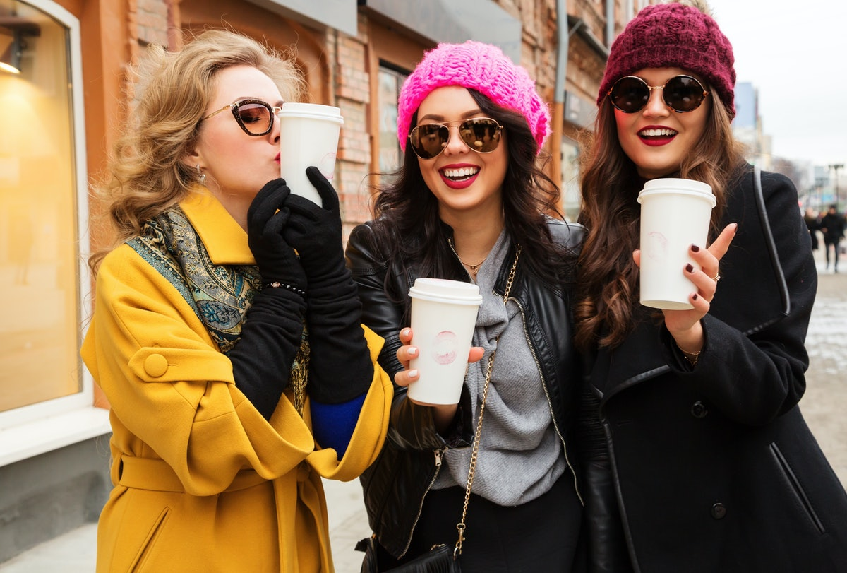 Outdoors fashion portrait of three young beautiful women friends drinking coffee. Smiling and going ...