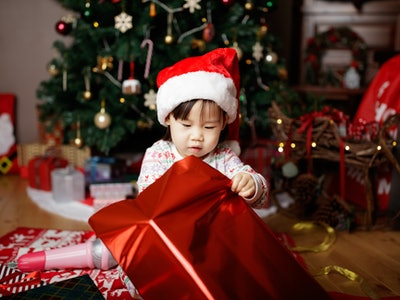 toddler baby girl wearing santa claus costume opening gift box  in front of christmas tree
