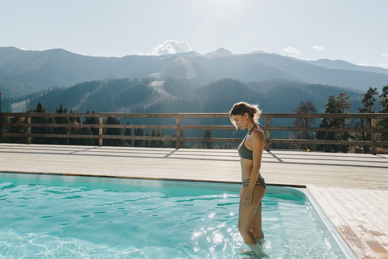 Young woman spending winter or spring vacation in luxury spa resort with swimming pool over alpine mountain landscape