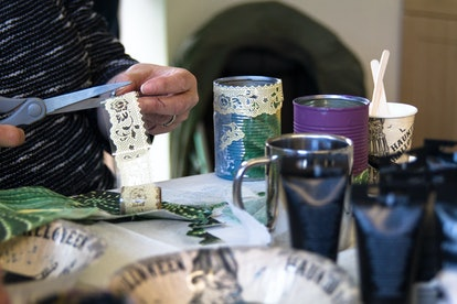 Recycling tin cans into decorated plant pots. Person cutting lace beside crafting table with crafting supplies on.  Crafting, recycling, gardening.