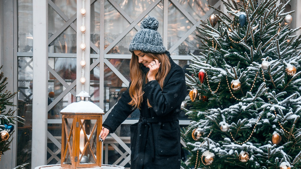 A woman with long, wavy hair and a black jacket poses next to a snowy Christmas tree and lantern in a Christmas town in the U.S.