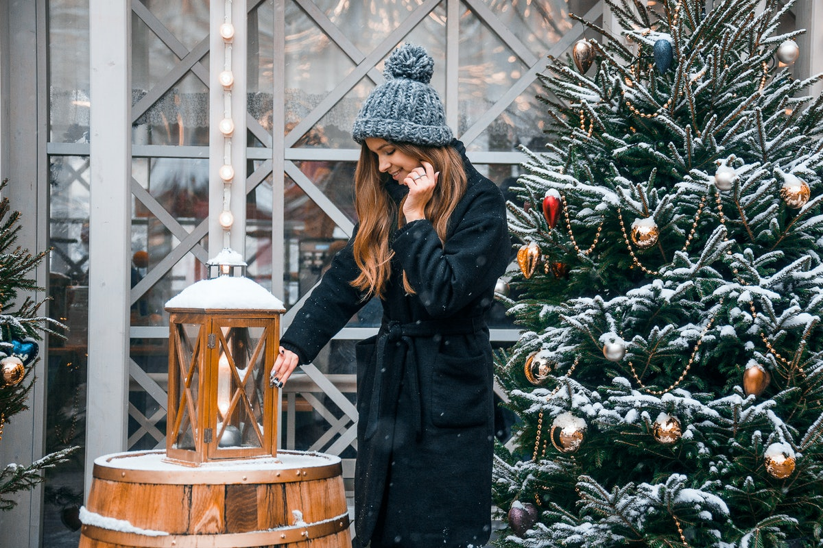 A woman with long, wavy hair and a black jacket poses next to a snowy Christmas tree and lantern in ...