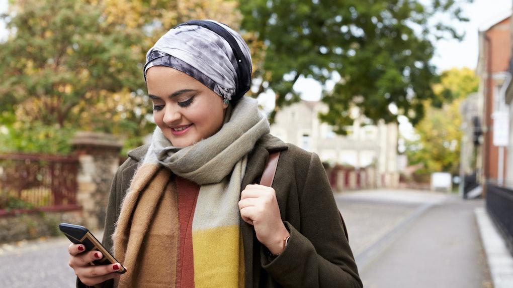 British Muslim Woman Using Mobile Phone In Urban Setting