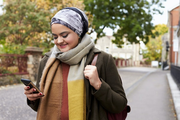 British Muslim Woman Using Mobile Phone In Urban Setting