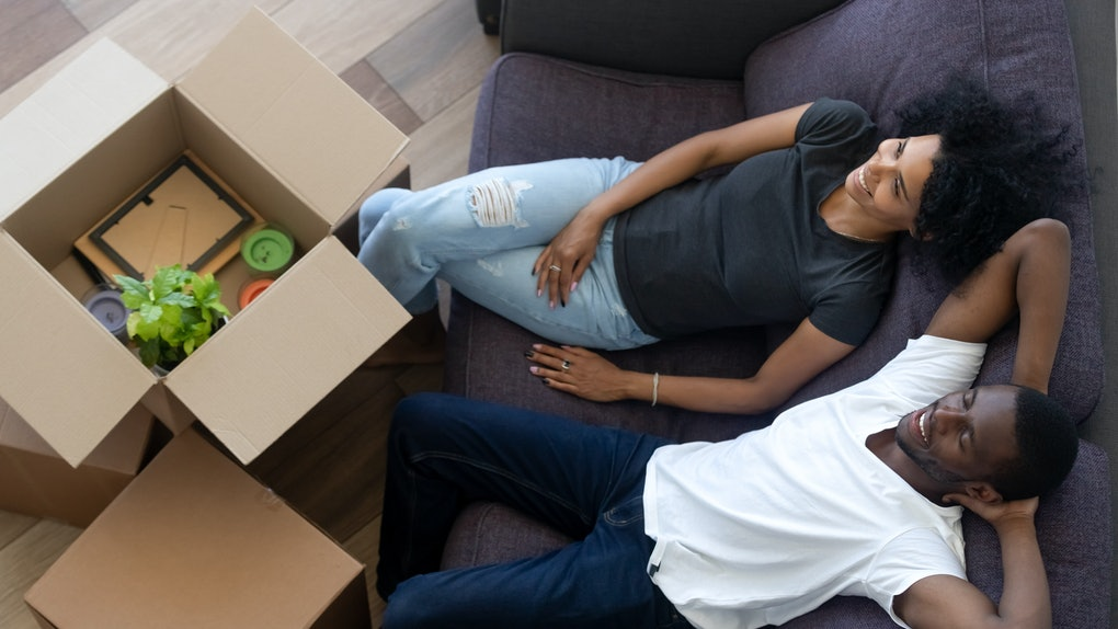 African american millennial couple relaxing on couch in new home, happy young black renters tenants owners resting on sofa with boxes after relocation concept in living room, moving day, top view